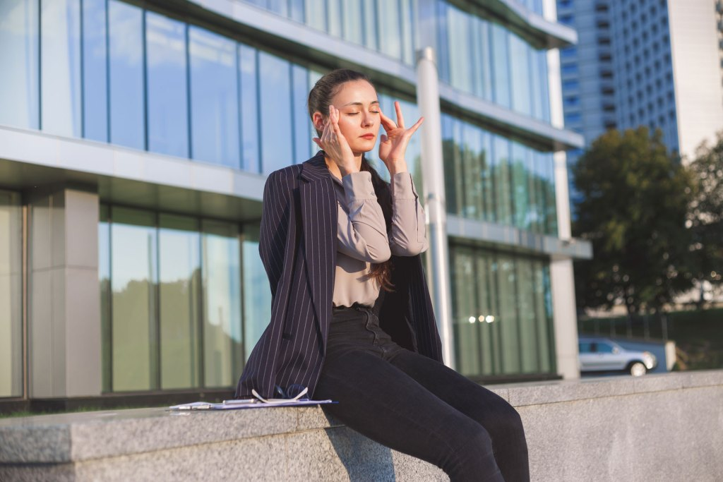 stressed out business woman sitting in front of office building