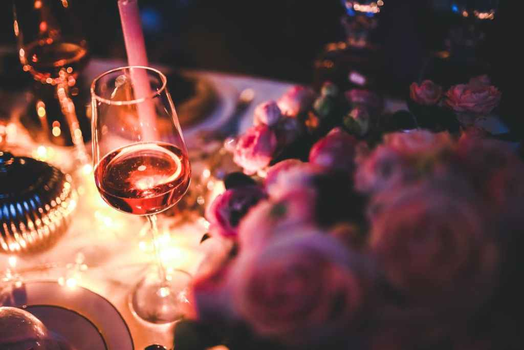 Wine glass and a candle on a table surrounded by flowers