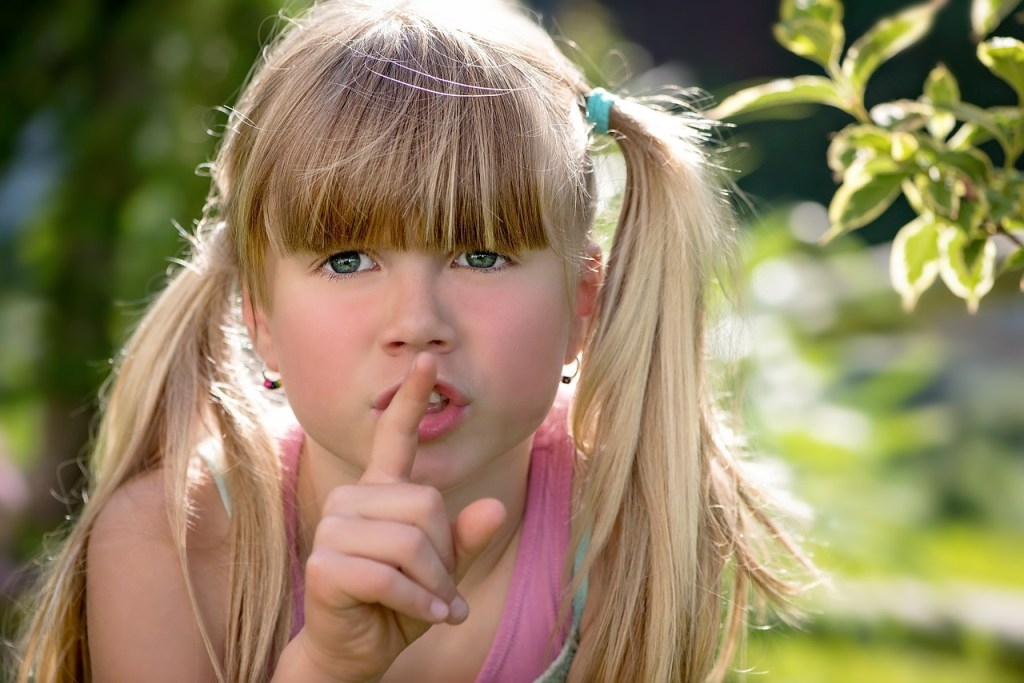 Child with finger to mouth in shh gesture