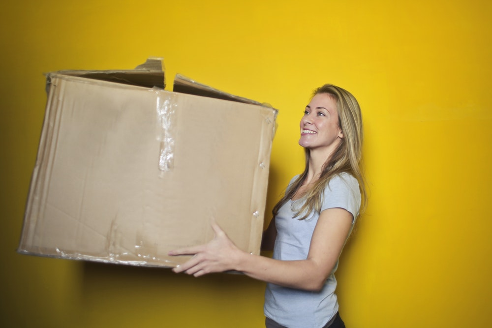 Smiling woman carrying a box