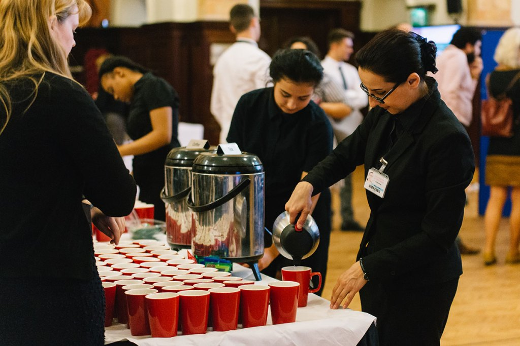 Caterers pouring coffee into mugs while at an event in the Great Hall