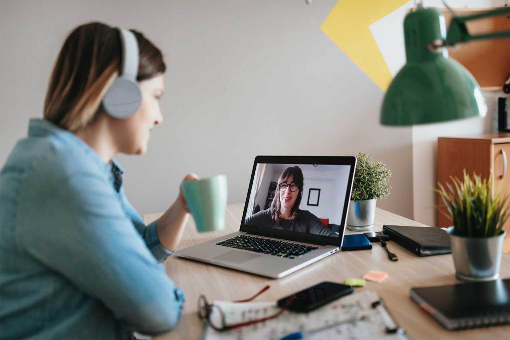 Woman teleconferencing with sister on laptop due to COVID-19 lockdown