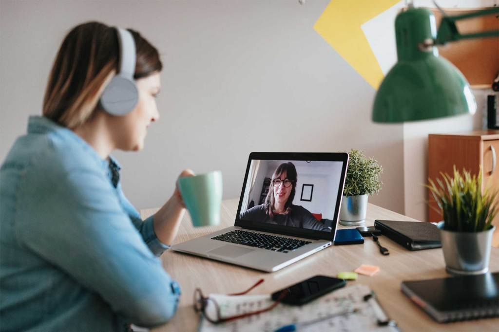Woman wearing headphones whilst attending a virtual meeting.