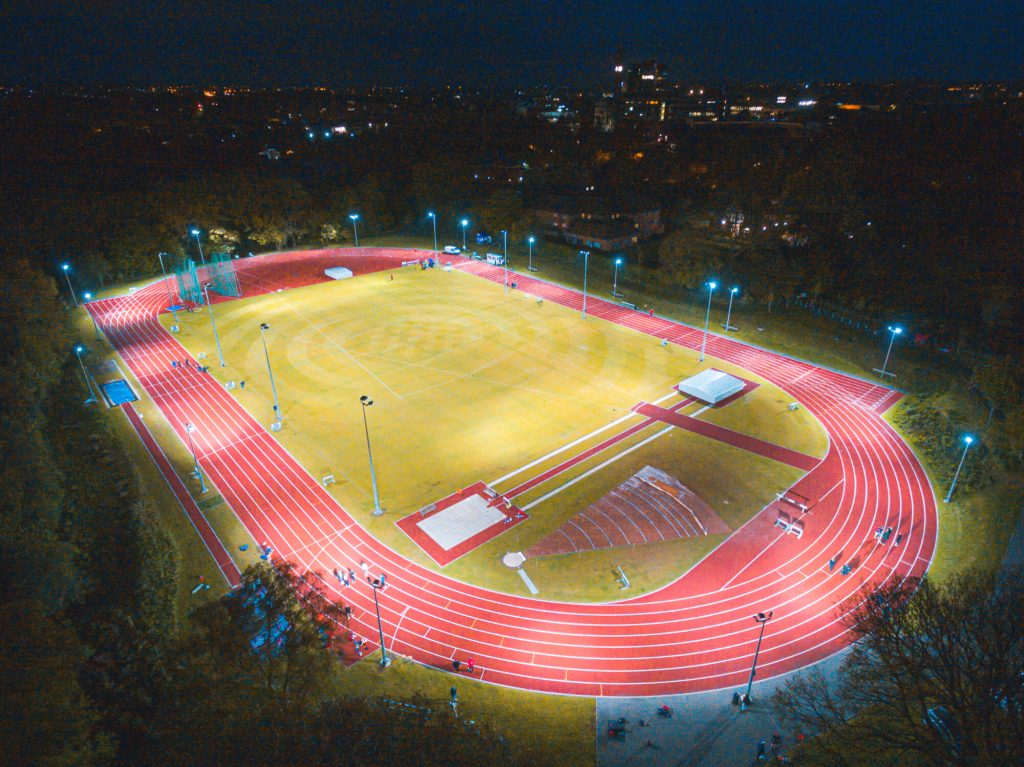Aerial view of the University of Birmingham's athletics track, lit at night