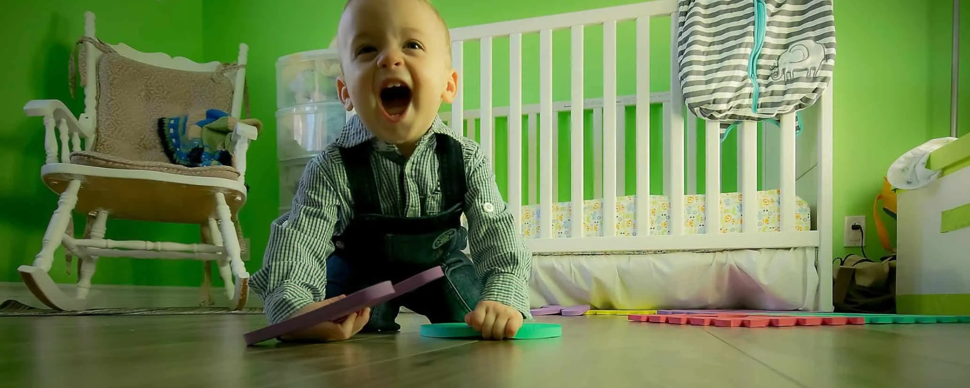 Baby crawling on floor yelling in front of crib