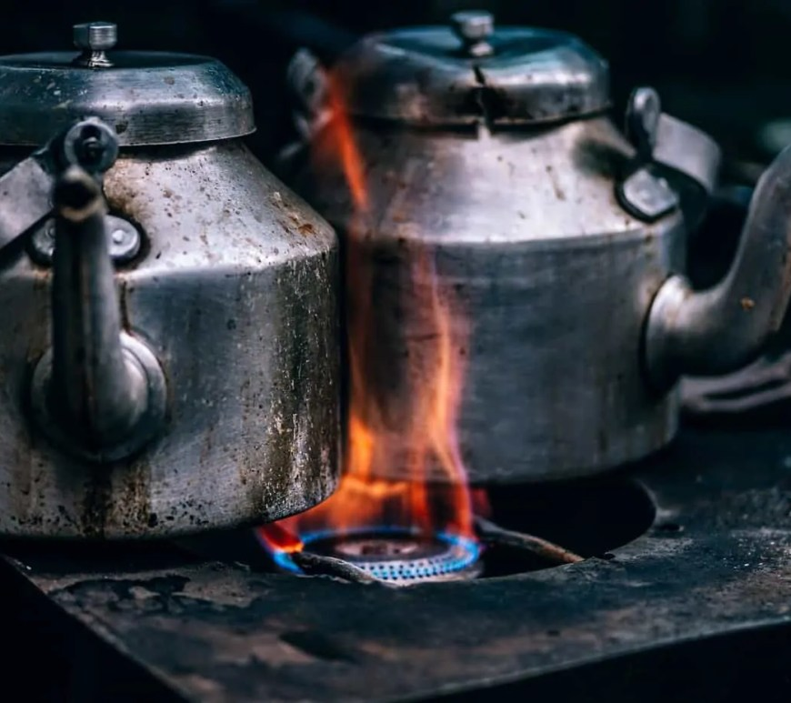 Two tea pots boiling on one gas burner
