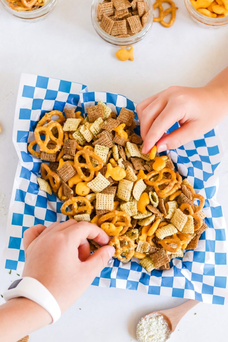 little hands grabbing air fryer Chex mix