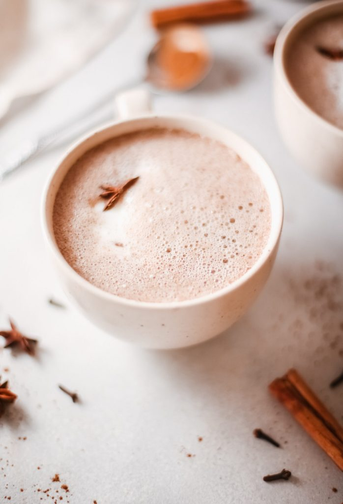 pumpkin spice hot chocolate with spices around the mug