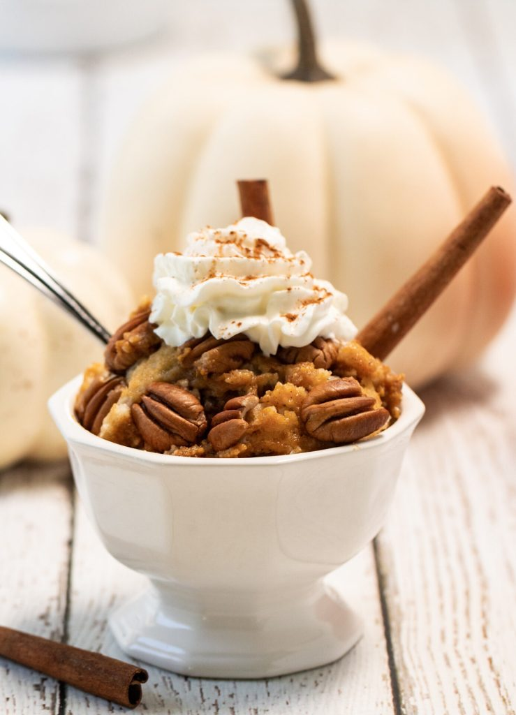 pumpkin cobbler in small dish with whipped cream and cinnamon sticks