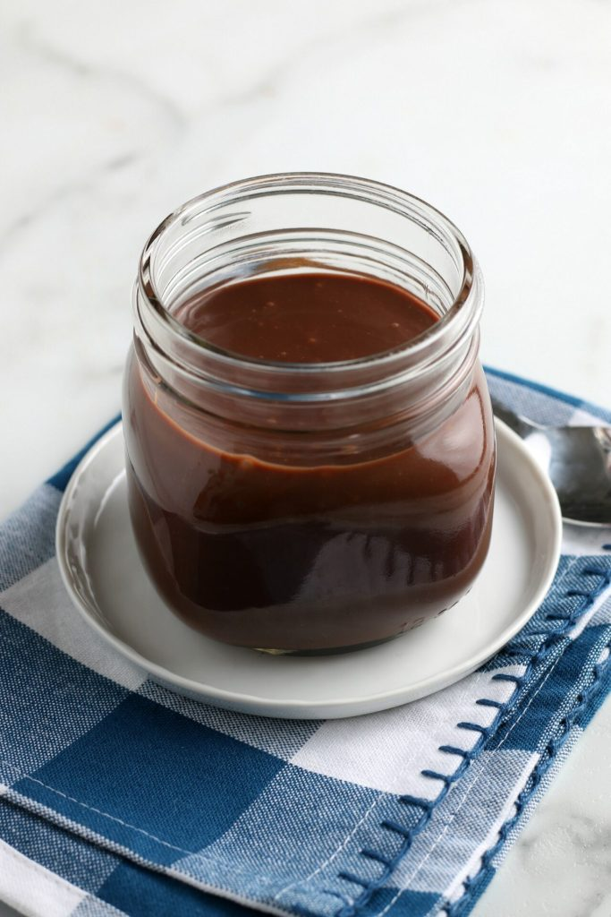 glass jar of chocolate sauce on a blue gingham towel