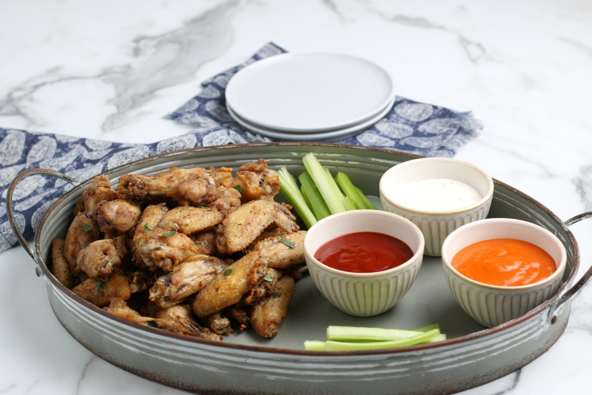 chicken wings on tray with celery and dipping sauces