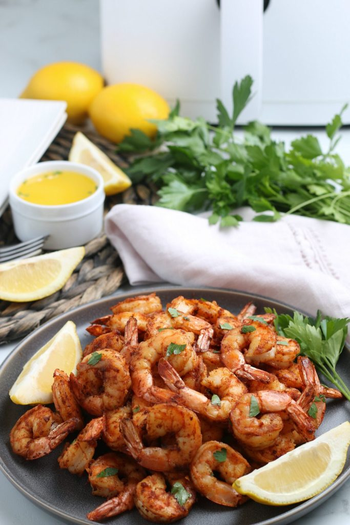 gray plate of shrimp with lemons, cilantro, and plates