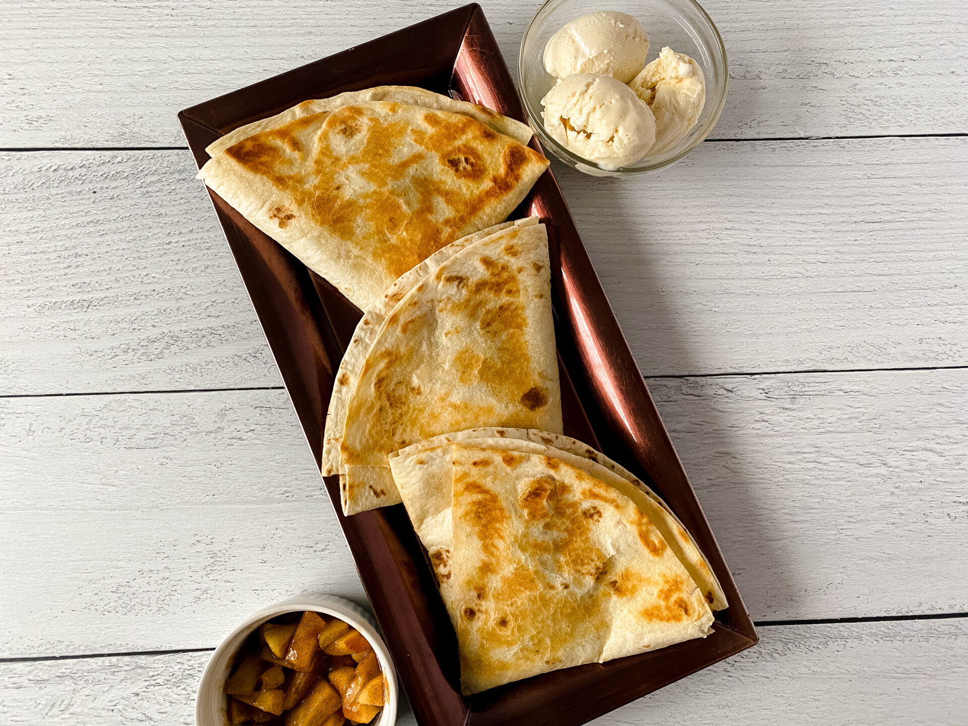 horizontal shot of apple pie tortilla wrap on red plate
