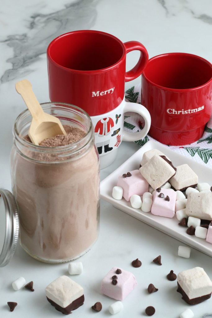 jar of homemade hot chocolate mix with wooden scoop and mix ins