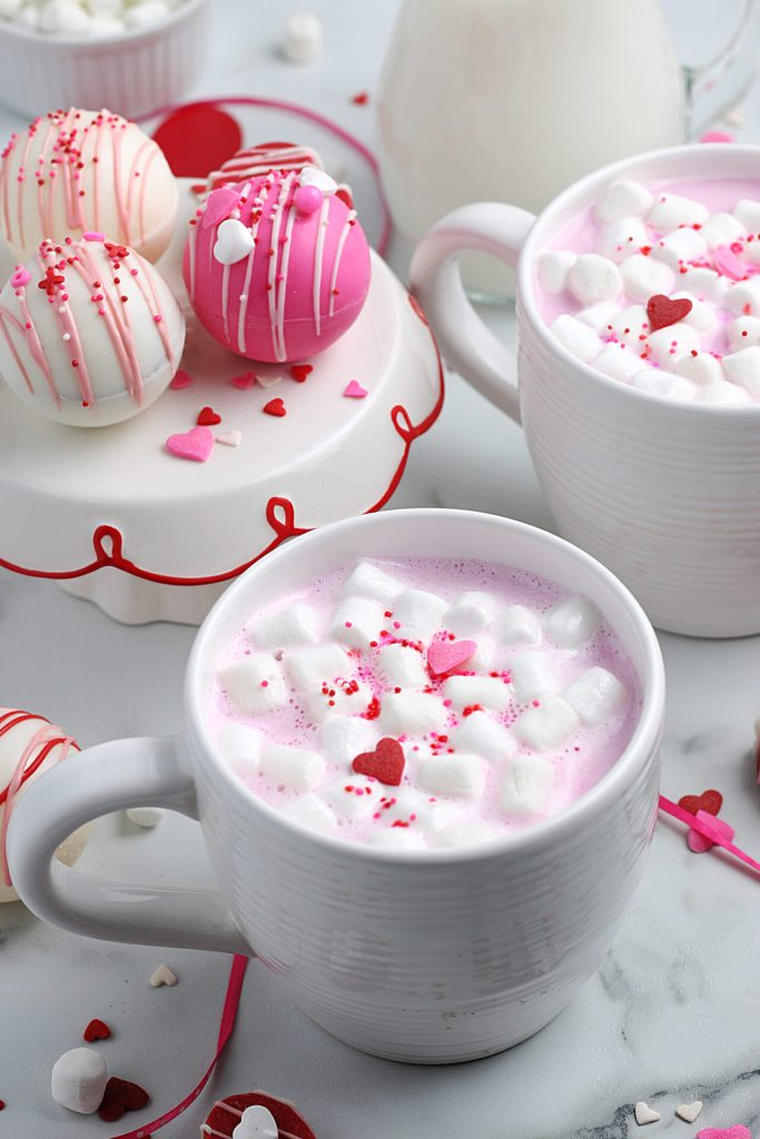 pink hot chocolate in white mug with serving tray full of pink hot chocolate bombs