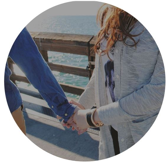 couple holding hands by ocean