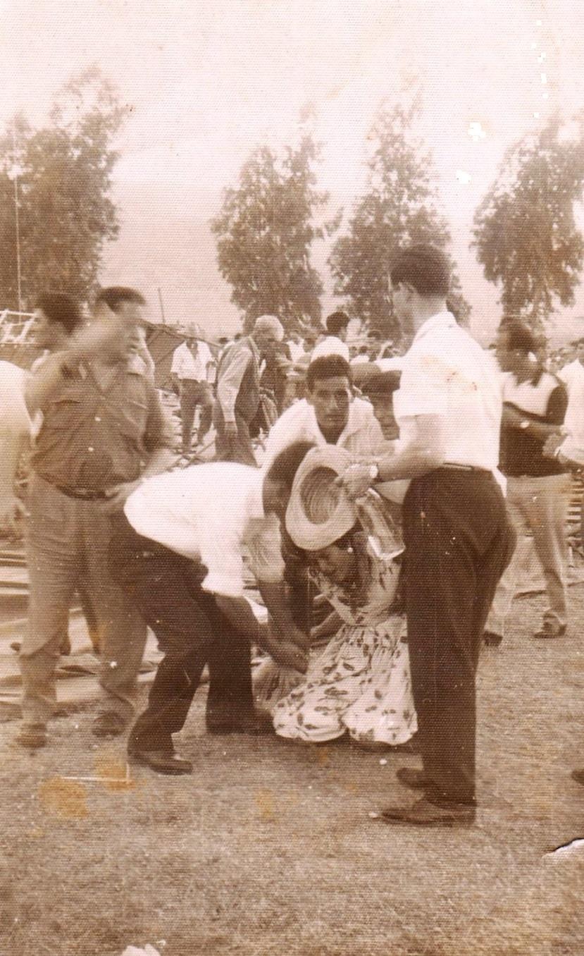 Una herida y contusionada siendo auxiliada. 17 de agosto 1961.