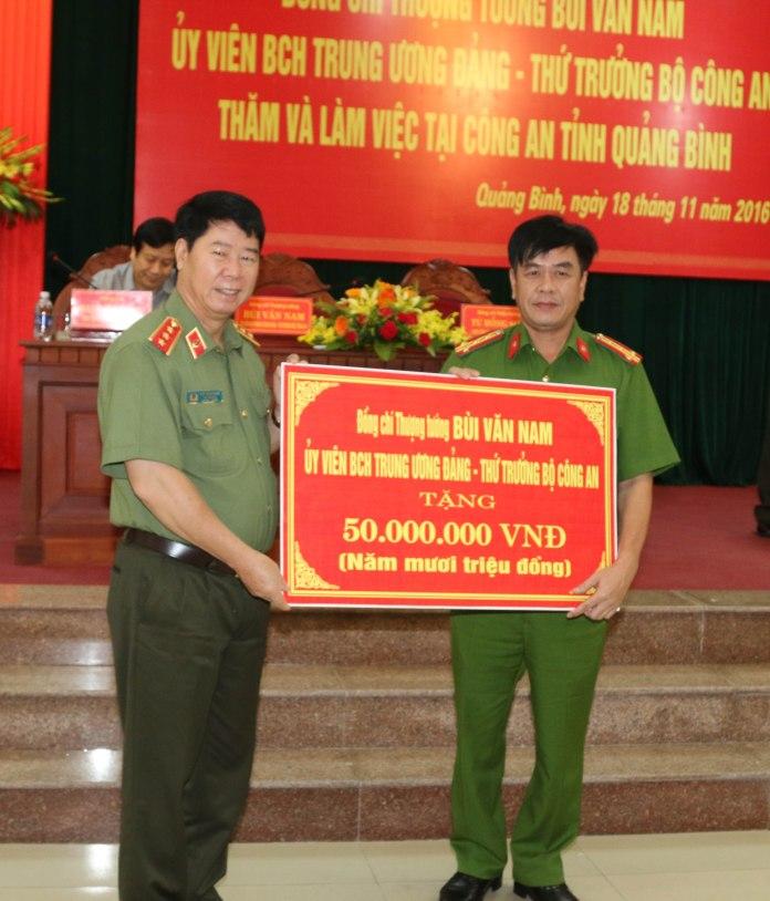 Đồng chí Thượng tướng Bùi Văn Nam, Ủy viên Trung ương Đảng, Thứ trưởng Bộ Công an trao tặng số tiền 50 triệu đồng cho Công an huyện Quảng Trạch, tỉnh Quảng Bình