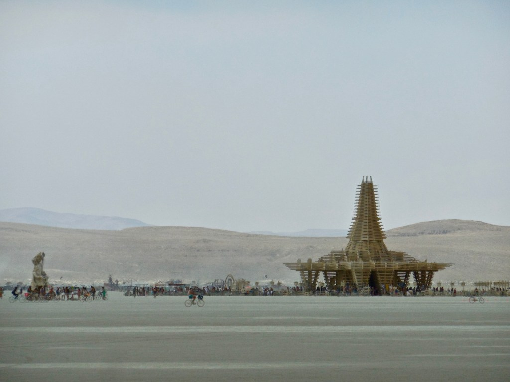 The figure to the left is a mobile art piece. She roamed the playa, dressed differently each day. She also attracted an entourage of bike riders.