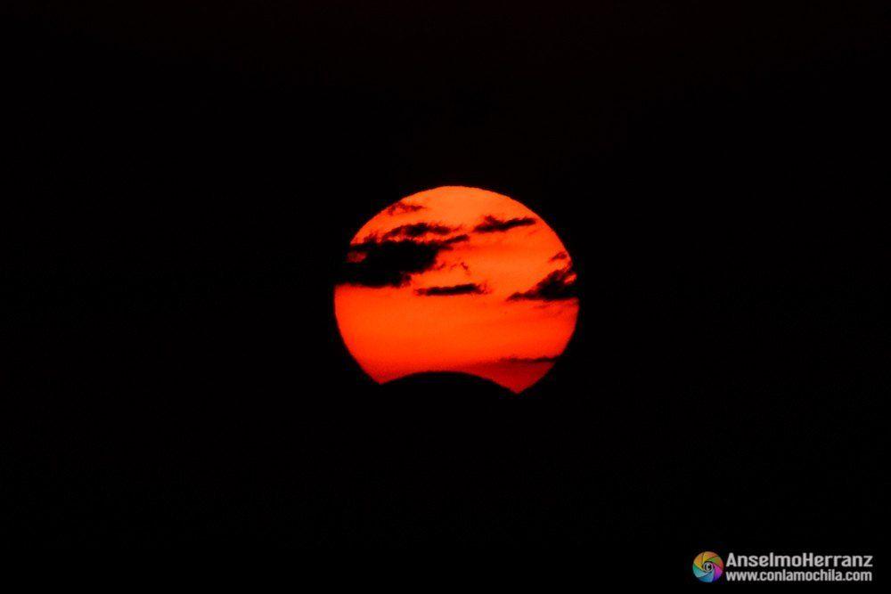 Eclipse solar. Las nubes le dan la apariencia de un lejano planeta al sol.
