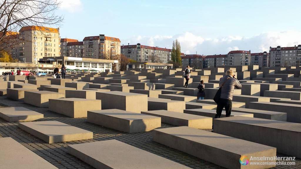 Algunos visitantes fotografiandose sobre los bloques de hormigon del monumento al Holocausto de Berlín