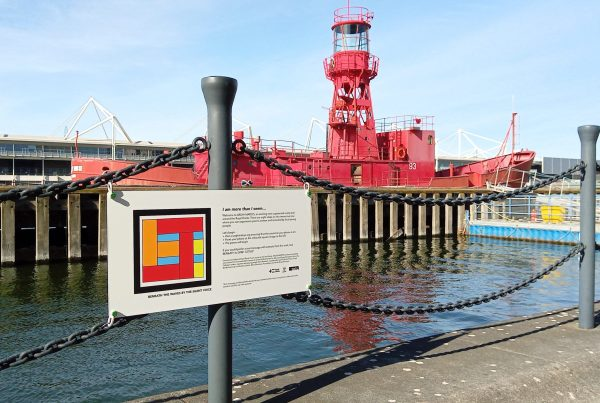 Photograph showing the installed sign with an AR marker designed by the Silent Voice for his poem titled Beneath the Waves