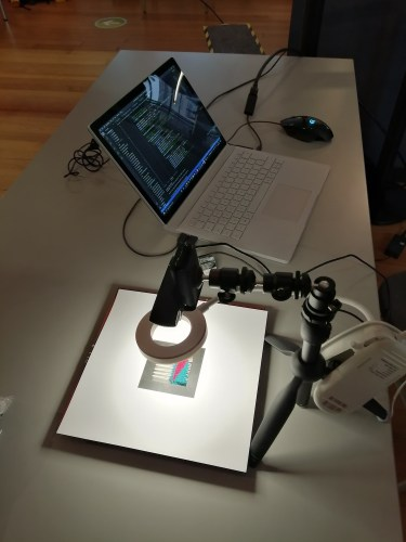 A web cam on an armature points downwards through a circle light to a woven sample beneath cutout card with a black square frame. The webcam is connected to an open laptop showing a page of code.