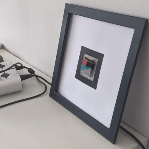 A square, blue picture frame leans against a wall. Inside the frame is a card cutout with another printed black square frame around a small woven marker.