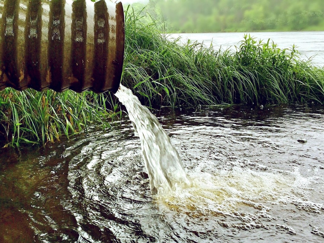 water gushing from a pipe into a stream