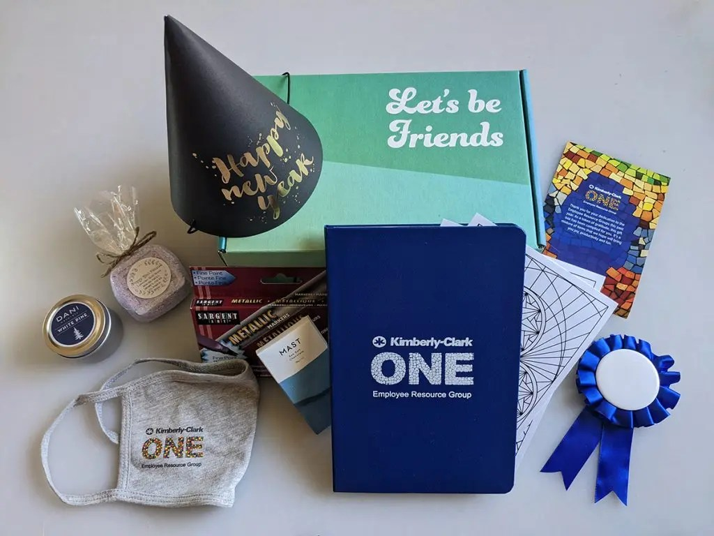 This small indulgences event Kit contained a sea salt chocolate bar, an aromatherapy candle, a bath bomb, some coloring sheets with metallic markers, a blue ribbon for attendees to make their own 2020 merit badge, a new years party hat, a client-branded notebook and facemask, and a postcard with a gratitude prompt on one side and an expression of thanks for the company to its team on the other.