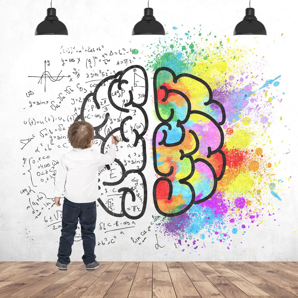 Rear view of a cute little boy wearing a white shirt and dark blue jeans writing or drawing with a marker. A concrete wall background with a colorful brain sketch on it.