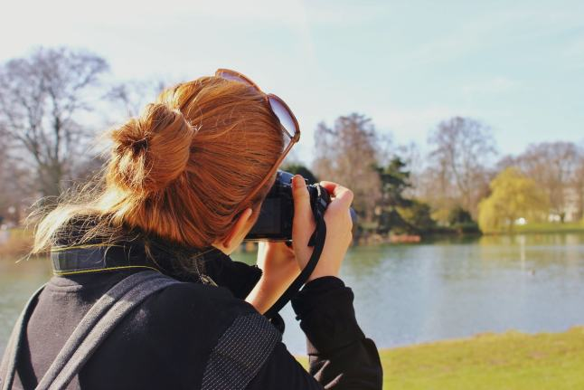 Woman holding a camera taking a picture of the view