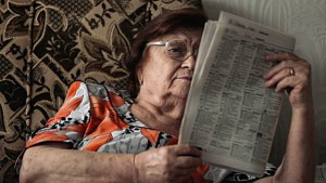 stock-video-90691035-old-woman-reading-newspaper-sitting-in-chair