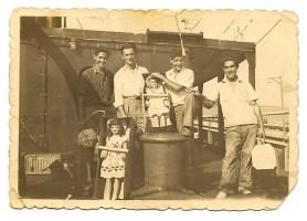 """Fecha: 15 de noviembre de 1949. Barco; tanque americano o petrolero. Desde la izquierda de la foto; Pepe Santana, a continuación cocinero del barco, Pedro Acosta """"Perico"""" y Juan """"El Porrón"""" último a la derecha con un bolso de mimbre. Pepe Santana porta un bolso de hoja de palma. Estos bolsos eran fabricados en la cárcel, y los familiares de los presos los vendían a los cambulloneros."""