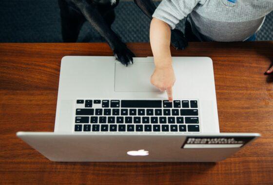 barn og computer trykker på tastatur