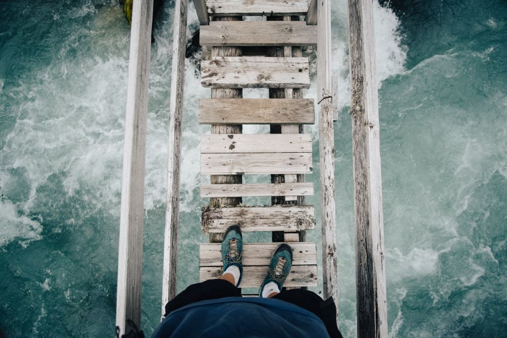 Meeting the fear of a layoff | man standing on wooden bridge over tumultuous water