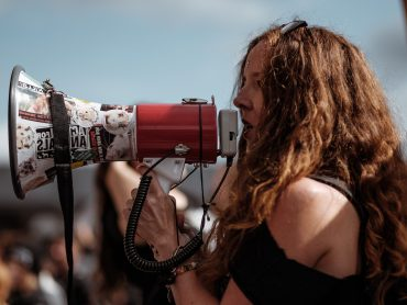 Turn helplessness into effective action | woman activist speaks into megaphone at crowded rally