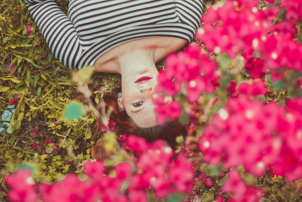 Woman lying under new flower blooms looking up at sky | Spring seasonal junction rebirth | Conscious Content