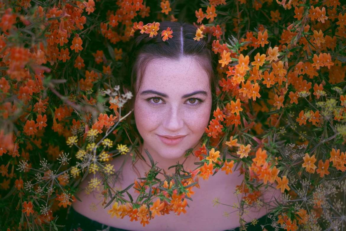 woman surrounded by bright flowers and herbs | get creative with your food ancient secrets of the astringent taste of spring | Conscious Content