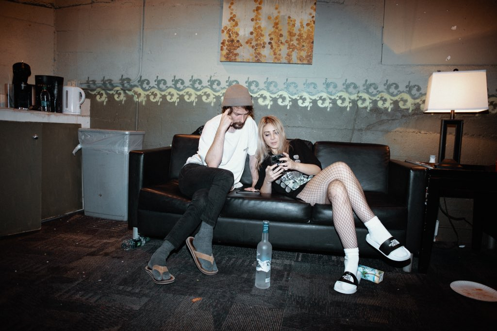 Chet Porter and Alison Wonderland look at phone together in green room