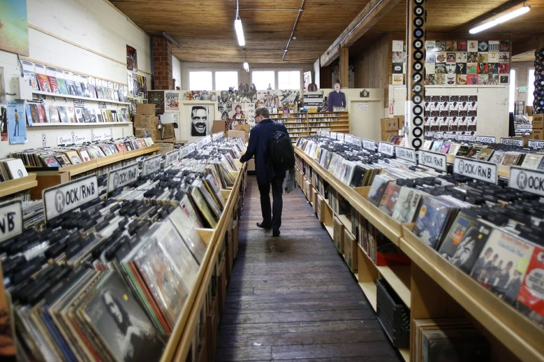 man shops at record store for vinyl 12""