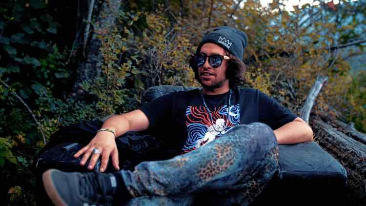 CharlestheFirst sitting against forest trees being interviewed by Shambhala Music Festival