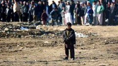 An Afghan child looks toward the site of a suicide bombing that occurred near a NATO convoy in Kabul, Afghanistan's capital, last February.