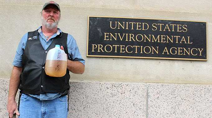 Ray Kemble of Dimock, Pennsylvania, holds a jug of discolored water from his well, contaminated by nearby fracking operations while standing outside of the U.S. EPA building in Washington, DC. Photo credit: Food & Water Watch