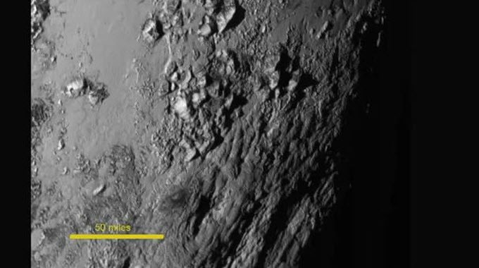 Close-up view of mountains on Pluto, which according to NASA reach up to 11,000 feet. There are no visible impact craters, NASA said, suggesting that the dwarf planet may be relatively young.