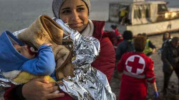 A Syrian woman holds her baby after their arrival on a small boat from the Turkish coast on the northeastern Greek island of Lesbos Monday, Nov. 16, 2015. (Photo: AP/Santi Palacios)