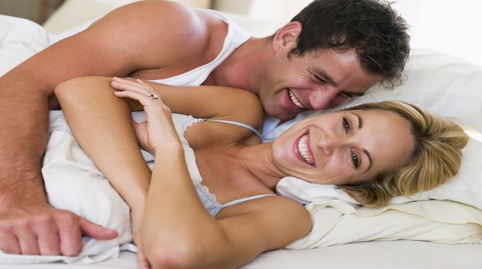 Couple in bed laughing-compressed (1)