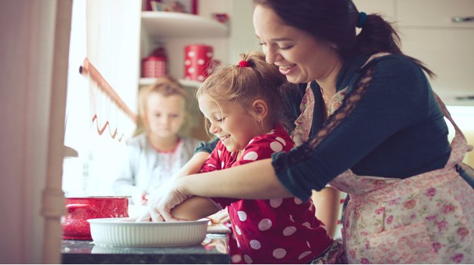 Woman cooking with daughter-compressed