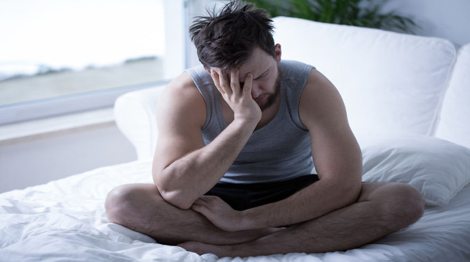 Man in bed looking distraught