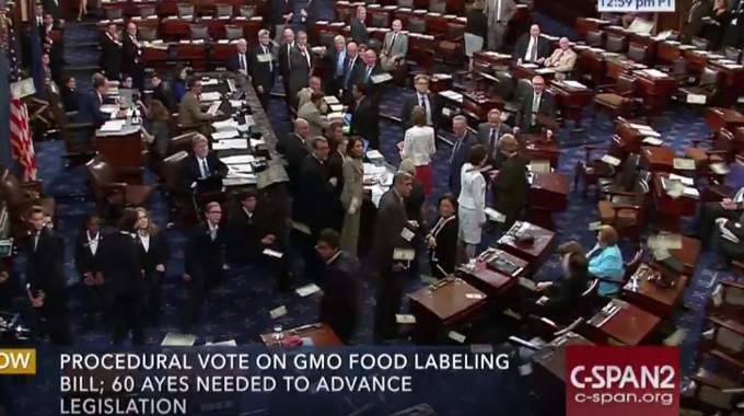 Money is thrown on the Senate floor during the GMO cloture vote to protest back-room dealings between senators and biotech lobbyists. (Screenshot)